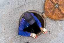 Working Man Comes Out From The Sewerage Hatch In The Ground On City Street