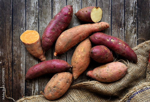 Fotomural  Mix of sweet potatoes with sack over wooden background