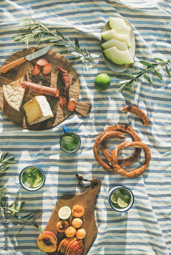 Keuken foto achterwand Picknick Flat-lay of summer picnic set with fruit, cheese, sausage, bagels and lemonade over striped blanket, top view, vertical