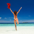 Happy young woman jumping on the beach. Happy lifestyle. White sand, blue sky and crystal sea of tropical beach. Vacation at Paradise. Ocean beach relax, travel to islands
