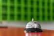 Closeup of a silver service bell on hotel reception desk. Concept asking for service