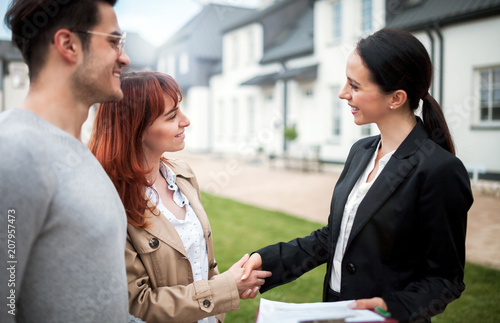 Fotografía  Real estate agent shaking hands with customers after buying new house in residen