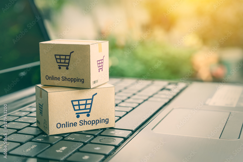 Fototapeta Online shopping / ecommerce and delivery service concept : Paper cartons with a shopping cart or trolley logo on a laptop keyboard, depicts customers order things from retailer sites via the internet.