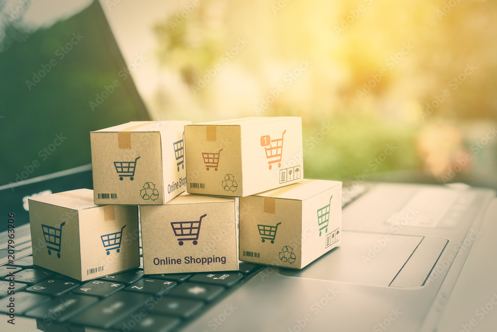 Fototapety, obrazy: Online shopping / ecommerce and delivery service concept : Paper cartons with a shopping cart or trolley logo on a laptop keyboard, depicts customers order things from retailer sites via the internet.