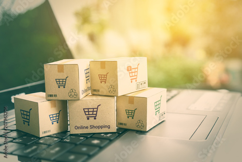 Fotomural  Online shopping / ecommerce and delivery service concept : Paper cartons with a shopping cart or trolley logo on a laptop keyboard, depicts customers order things from retailer sites via the internet