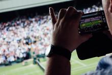 Spectator Watching Tennis And Taking Photo
