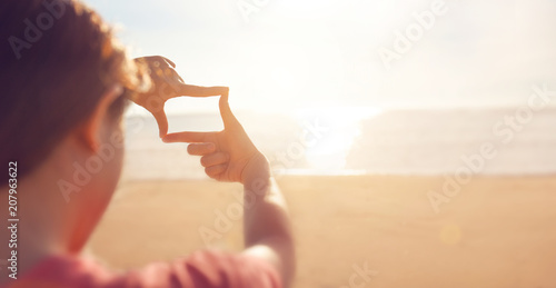 Obraz Future planning, Close up of woman hands making frame gesture with sunrise on sea summer, Female capturing the sunrise, sunlight outdoor. - fototapety do salonu