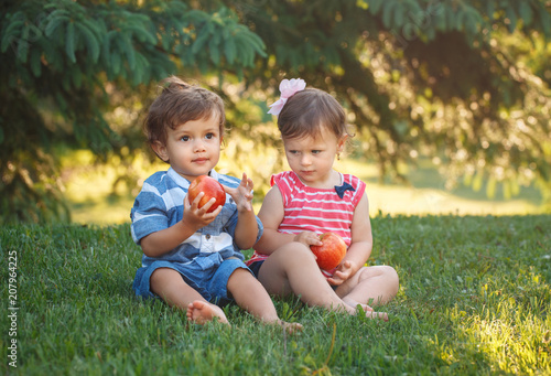 Photo Group portrait of two white Caucasian cute adorable funny children toddlers sitting together sharing apple food