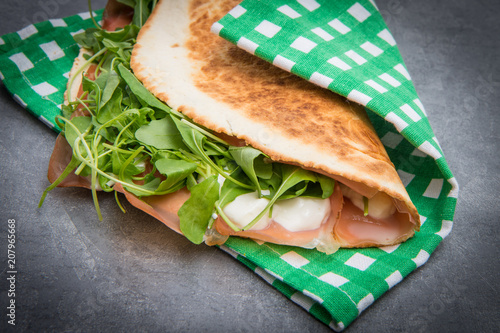 typical piadina romagnola with ham, cheese and rocket