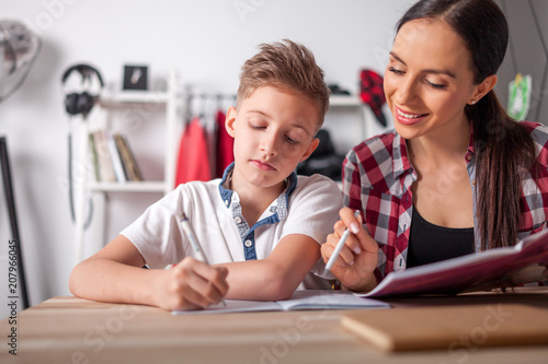 Photo Mother helping her son with homework in teenage room at home