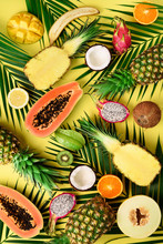 Exotic Fruits And Tropical Palm Leaves On Pastel Yellow Background - Papaya, Mango, Pineapple, Banana, Carambola, Dragon Fruit, Kiwi, Lemon, Orange, Melon, Coconut, Lime. Top View.