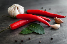 Red Chili Peppers, Garlic, Bay Leaf, Rosemary And Various Spices On Black Wood  Background