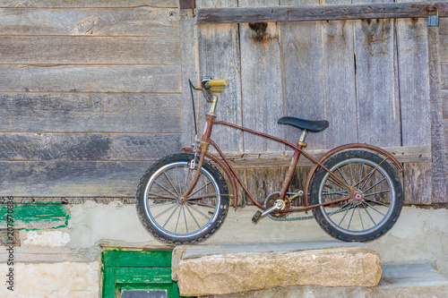 Spoed Foto op Canvas Fiets Old rusty children's bicycle near the wooden wall of an old house