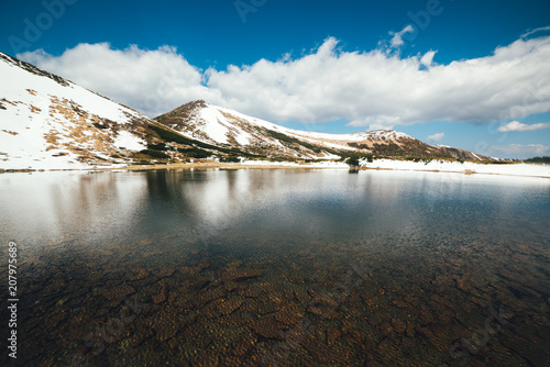 Spoed Foto op Canvas Canada Frozen mountain lake with blue ice and cracks on the surface. Picturesque winter landscape with snowy hills under a blue sky, Carpathian mountains, Europe