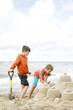 Cute children building sandcastle
