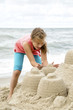 Joyful girl building sandcastle
