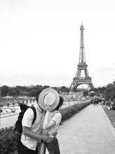 Couple Kissing In Front Of Eiffel Tower In Paris