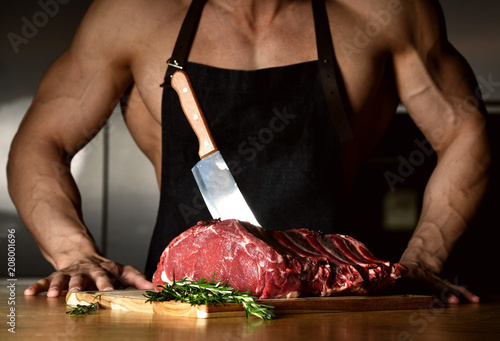 Fotografie, Obraz  Strong sport man prepare cook beef steak ribs on dark kitchen background healthy
