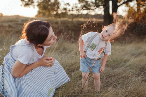 Curious little boy explore spider's web with his mother outdoors