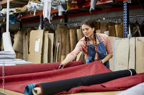Tuinposter Stof Female Worker Cutting Fabric In Sofa Workshop