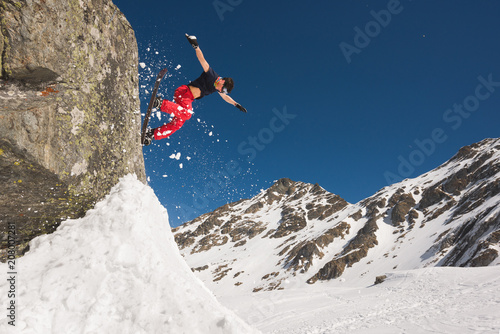 Papiers peints Glisse hiver Snowboarder jumping off cliff scattering the snow