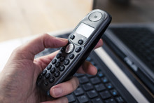 Hand Holding A Black Cordless Telephone With Laptop At Background