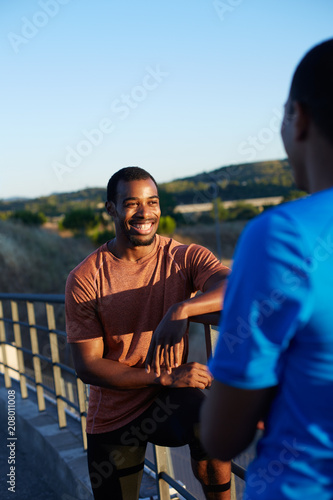 Papiers peints Detente Two african american friends wearing sports clothes in a relax moment of their workout chatting outdoors