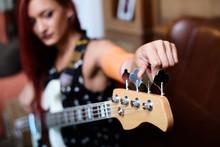 Unfocused Girl Tunes Electric Guitar.