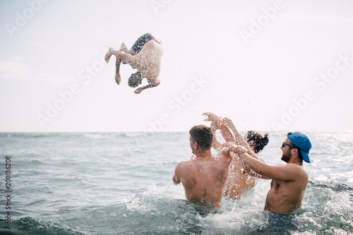 Group of friends throw their friend into water