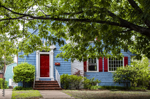 Fotografía Cute brightly painted blue shingled cottage with red and white trim under a big