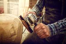 Close Up Of A Carpenter, Builder In Work Clothes Saw To Cut Out Sculpture From Wooden A Man's Head  In The Workshop, Around A Lot Of Tools,wooden,furniture For Work