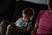Toddler Watching Cartoons On Computer Tablet With Headset