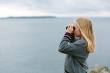 Little Girl Looking Through A Pair Of Binoculars On The Coast.