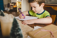 Little Boy Sitting At The Kitchen Table Signing Christmas Cards