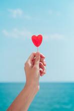 Hand Holding A Red Heart Lollipop