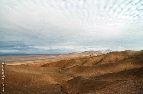Stunning view to the desert - cloudy sky, mountains and arid soil