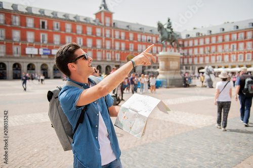 Foto  good looking young man traveler holding up a map in madrid
