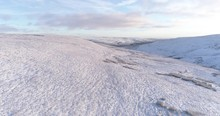 Aerial Shot Of Flying Over Snow Covered Valley In North Yorkshire.