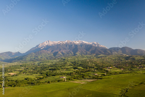 Foto op Plexiglas Europa spring landscape with the mountain peaks covered with snow and clouds. aerial view by drone