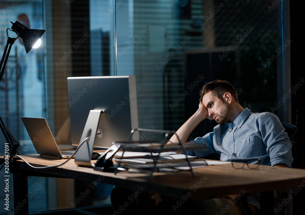 Fototapeta Casual man looking fatigue while working with computer in dark office alone.