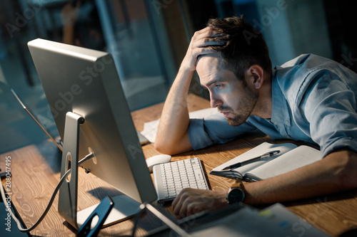 Young man leaning on hand looking extremely tired while finishing overtime project watching computer at table Fototapeta