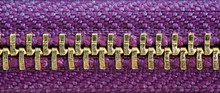 Purple And Gold Zipper Tightly Closed Binding Together Two Layers Of Fabric Textile Under High Magnification Close Detail Photography As Texture Background.