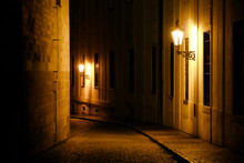 Old Lanterns Illuminating A Dark Alleyway Medieval Street At Night In Prague, Czech Republic. Low Key Photo With Brown Yellow Tones From The Lanterns As Single Light Sources Against The Dark Shadows