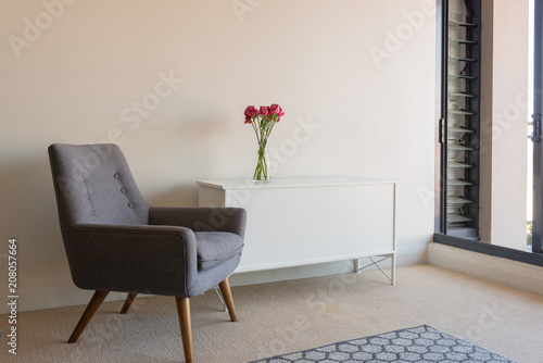 Fotografia, Obraz  View of living room with retro grey armchair and white sideboard with red roses