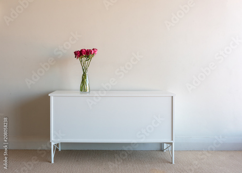 Fotografering Variegated red roses in glass vse on white sidetable against neutral wall backgr