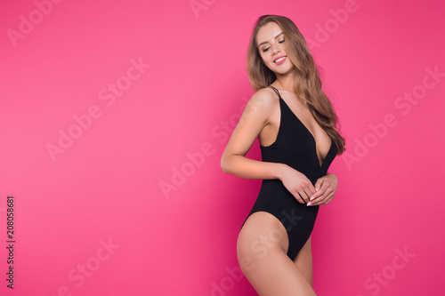 Tuinposter Akt Enjoy yourself! Close up photo of the cheerful attractive young woman wearing black sexual lingerie posing at the camera.