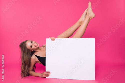 Poster Akt In a mood of total nudity! Attractive cheerful well-graced lady pleasantly smiling, while holding up her legs, while sitting on the floor with white board.