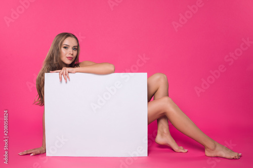 Poster Akt Wear something a little sexy! Young well-graced attractive girl wearing stylish lingerie and sitting on the floor, while holding empty blank board on the pink background.