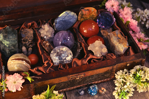 Close up of box with magic crystals and stones, sakura spring flowers on planks. Occult, esoteric and divination still life. Halloween background with vintage objects
