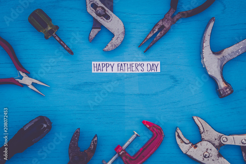 Happy Father's Day still life concept with worn tools on blue board, flat lay in vintage tones